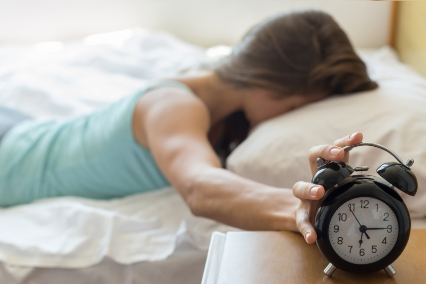 Wake up of a girl stopping alarm clock